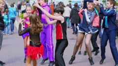 Several kids in colorful suits dance on street among people Stock Footage