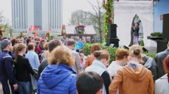 Crowd of people watch singer performance on stage at spring sunny day Stock Footage