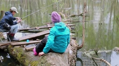 Children boy and girl fishing on trunk near pond at spring day Stock Footage