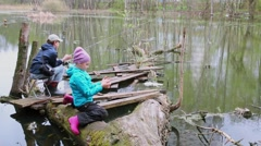 Two kids boy and girl fishing on trunk near pond at spring day Stock Footage