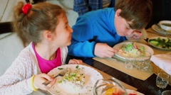 Two kids boy and girl eat meals at restaurant table Stock Footage