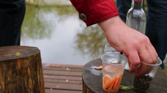Man takes some oiled bran as snacks for drinks near wavy water of pond Stock Footage