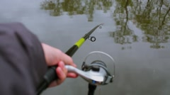 Hand holds fishing stick above wavy water with reflection of trees Stock Footage