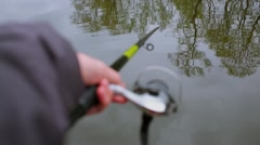 Hand with fishing stick above pond water with reflection of trees Stock Footage