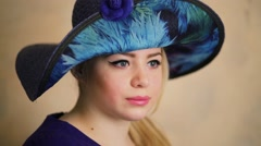 Face of young woman in big blue hat closeup at studio Stock Footage
