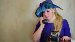 Blonde in big blue hat speaks by retro phone at studio Stock Footage