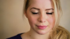 Beautiful young woman with blond hair smiles closeup in studio Stock Footage
