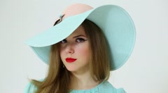 Face of cute young woman in big cyan hat closeup at studio Stock Footage