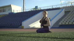 Young athlete woman sitting on the lawn in the stadium - stock footage