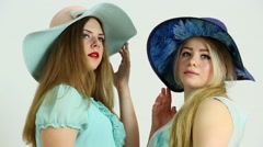 Pair of women in big hats smile and look on each other in studio Stock Footage