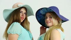 Pair of attractive women in big hats smile and walk away in studio Stock Footage