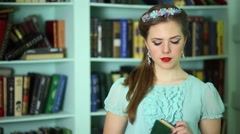 Beautiful young woman with jewellery on head opens book in library Stock Footage