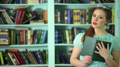 Beautiful young woman puts book on shelve in library Stock Footage