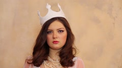 Young woman looks forward with crown on head and necklace Stock Footage