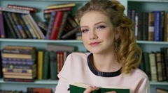 Young woman holds book near book shelves in library Stock Footage