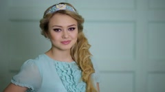 Young blonde smiles in blue dress and diadem on head Stock Footage
