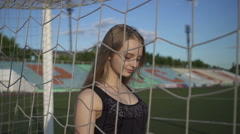 Young woman athlete goes football field and touches the net gate Stock Footage