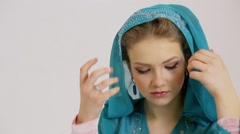 Young woman puts off and then returns hood of cyan dress Stock Footage