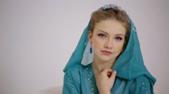 Young woman look around in cyan dress with hood and diadem on head Stock Footage