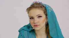 Profile of woman look aside in dress with hood and diadem on head Stock Footage