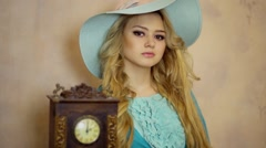 Blonde with curly hair touches retro clock in studio Stock Footage