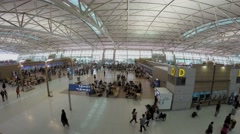 Many people walk by large hall of airport. Timelapse Stock Footage
