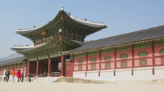 Many people walk near entrance of Geyongbokgun Palace at autumn Stock Footage
