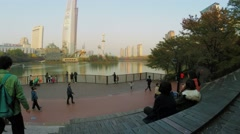 Many people walk in park with Lotte World amusement park on pond Stock Footage