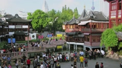 Yuyuan Garden with people which walk by 9 Turns bridge on pond Stock Footage