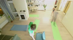 Five people makes yoga asanas in flat hall near kitchen. Timelapse Stock Footage