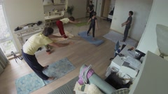 Four people family makes yoga asanas with instructor in flat hall. Stock Footage