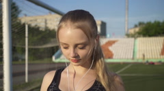 Young woman athlete goes through the stadium with headphones in their ears Stock Footage
