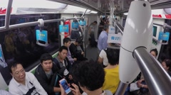 Many people ride in metro train by tunnel with commercial banners. Stock Footage