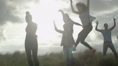 4K Happy carefree young friends dancing on the beach as the sun begins to set Stock Footage