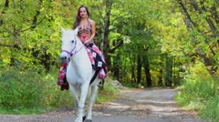 Young woman in gipsy dress rides on white horse by alley in park Arkistovideo
