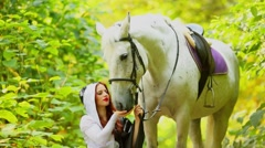 Beautiful woman in black and white dress holds horse among plants Stock Footage
