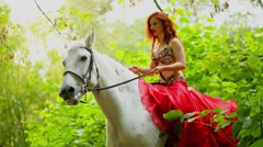 Beautiful young woman in red dress rides on white horse among leaves Stock Footage