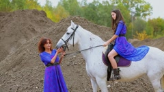 Mother and her daughter pat white horse near pile of ground Stock Footage