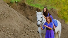 Mother holds horse with daughter sits on saddle near pile of ground Stock Footage