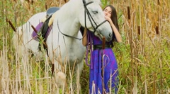 Girl in blue dress pats white horse among sedge at autumn day Stock Footage