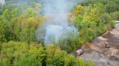 Fire truck stands near forest with smoke among tress at autumn Stock Footage