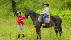 Cowgirls mother and her daughter on black horse at autumn day in park Stock Footage