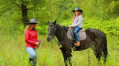 Woman and her daughter in black hats walk with black horse Stock Footage
