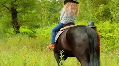 Young girl sits on black horse which is leaded by her mother Stock Footage