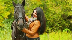 Brunette smiles and pats chestnut horse at autumn day in park Stock Footage