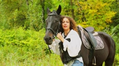 Woman with curly hair holds bay horse at autumn day in park Stock Footage