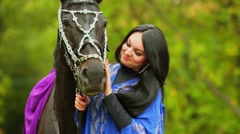 Brunette in blue clothes pats chestnut horse at park Stock Footage
