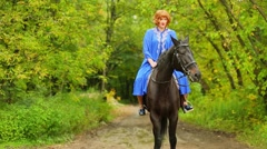 Red-haired woman in blue cloak rides on bay horse by park alley Stock Footage