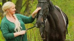 Woman with blond hair holds and pats bay horse at autumn day in park Stock Footage