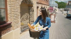 Brunette girl smiling to camera walks her bike with flowers and French bread Stock Footage